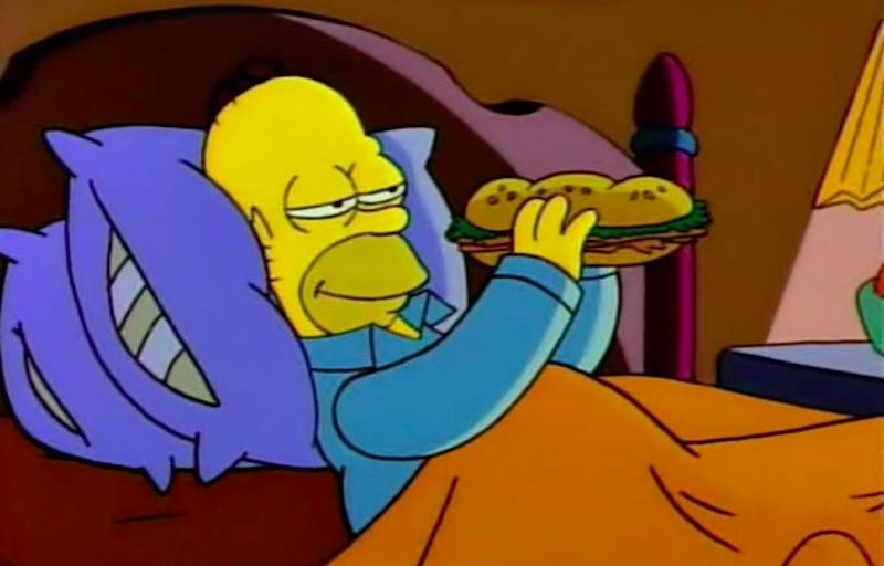 Man eating sandwich in bed